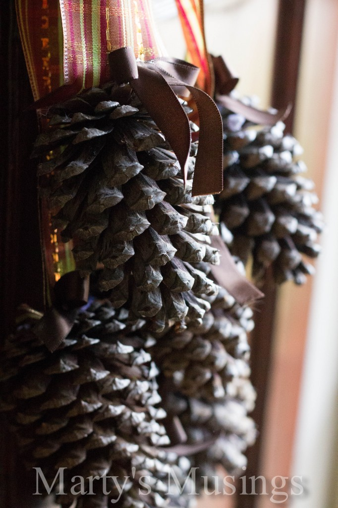 Group of pinecones photographed close up attached by small ribbon ribbon to striped glitter ribbon and hung on a wooden door