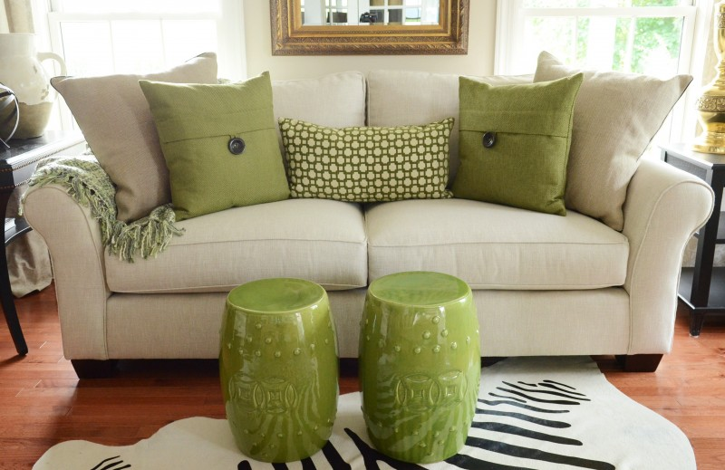sofa with green pillows and a multicolored green throw