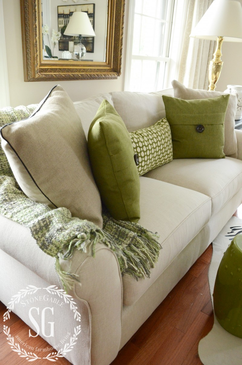 Neutral And Green Pillows On A Sofa With Throw