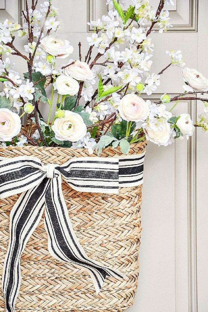 BASKET FILLED WITH SPRING FLOWERS ON A FRONT DOOR