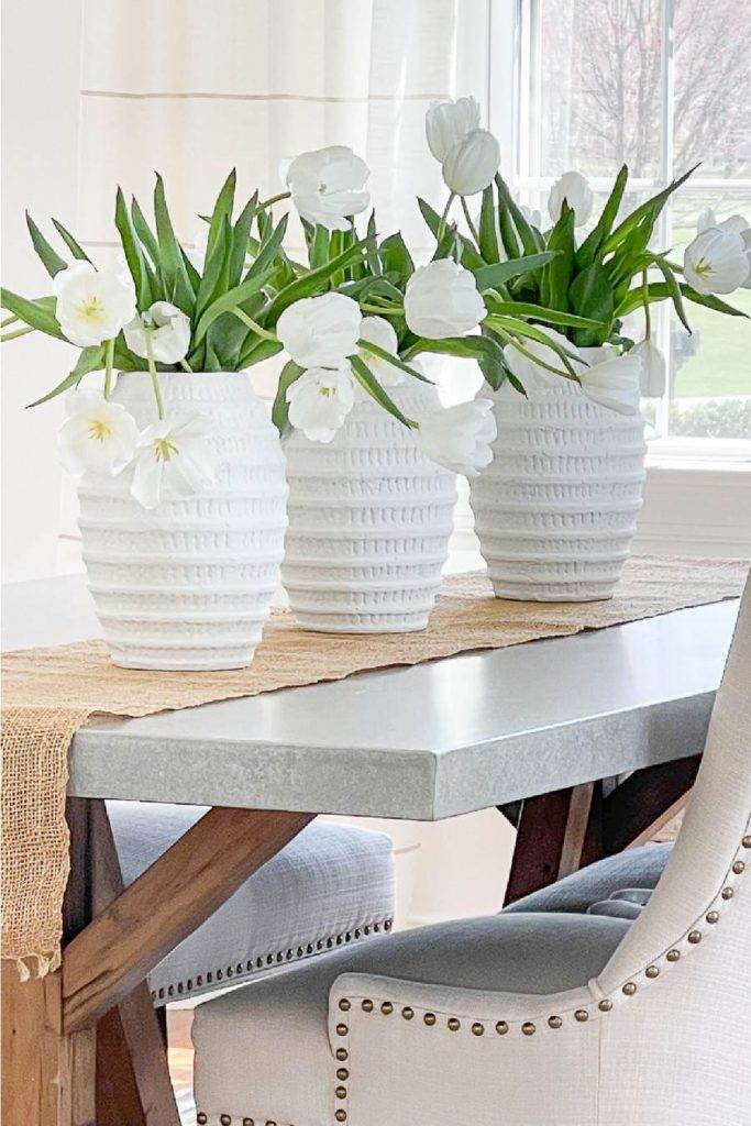 a trio of white vases filled with tulips