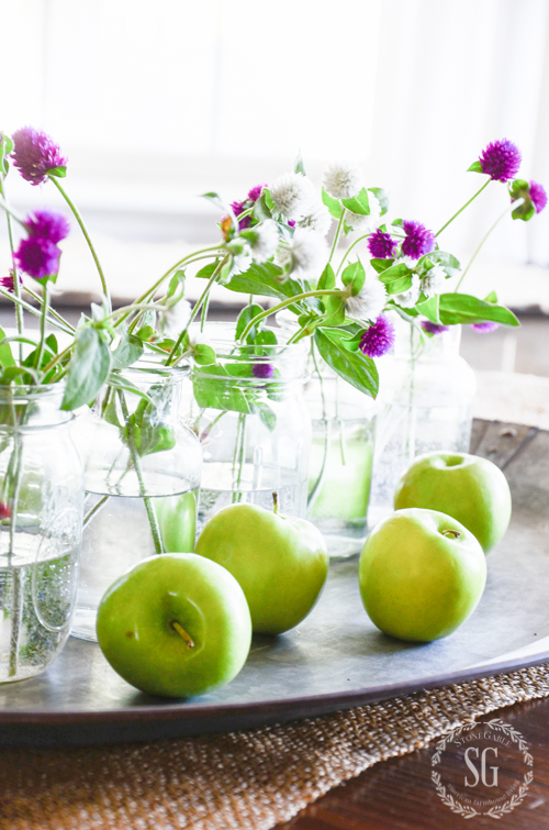 early fall centerpiece made with green apples on a galvanized tray and garden flowers in mason jars