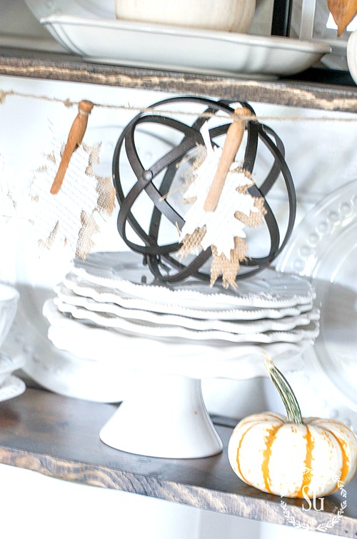 FALL OPEN SHELVES- White dishes, fall accents and burlap leaves.