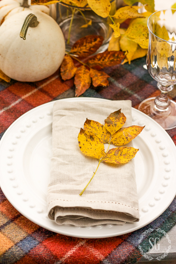 white dish with a beige linen napkin on a Thanksgiving table
