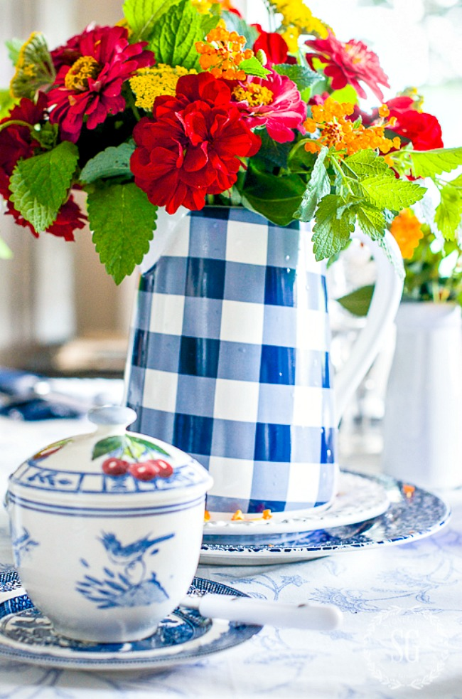 blue and white checkered coffee pot filled with garden flowers