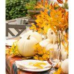 An outdoor table with with pumpkins and gold leaves
