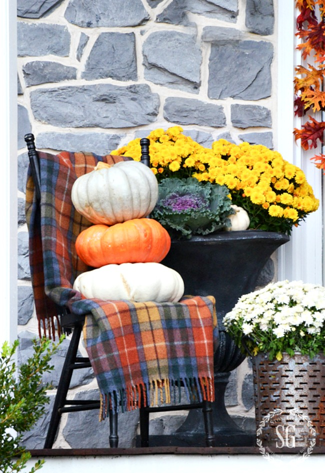 chair with tartan blanket and a stack of three pumpkins