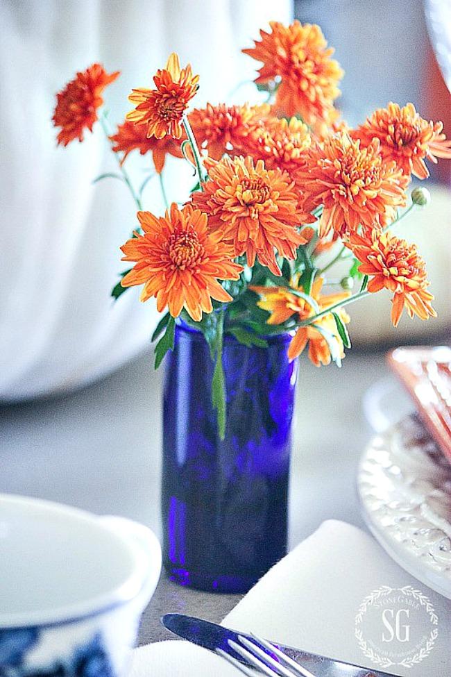 little cobalt blue vase filled with orange mums