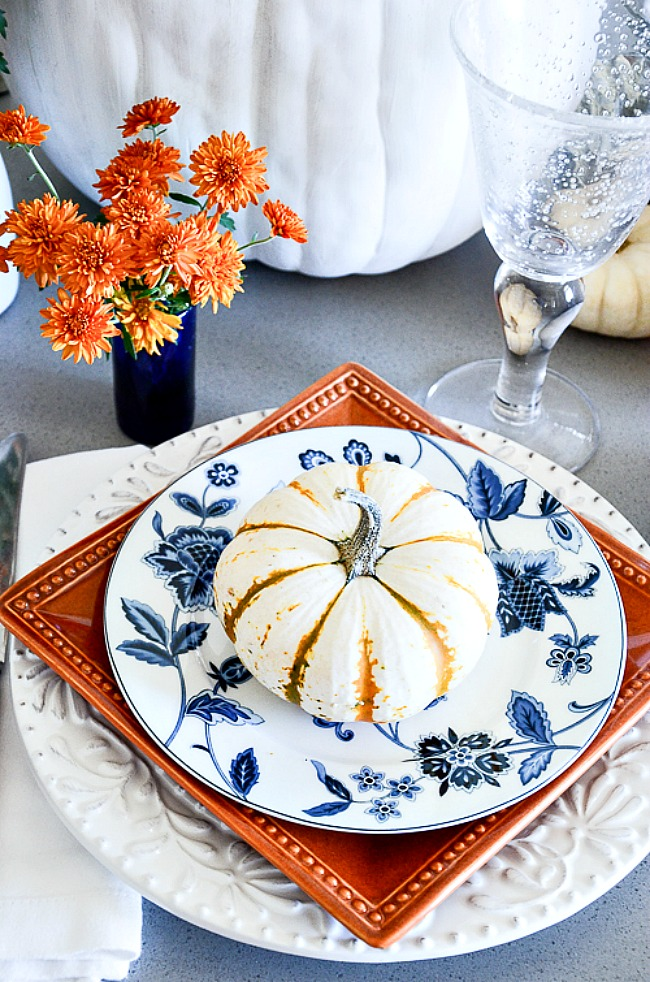table set with white, burnt orange and blue dishes