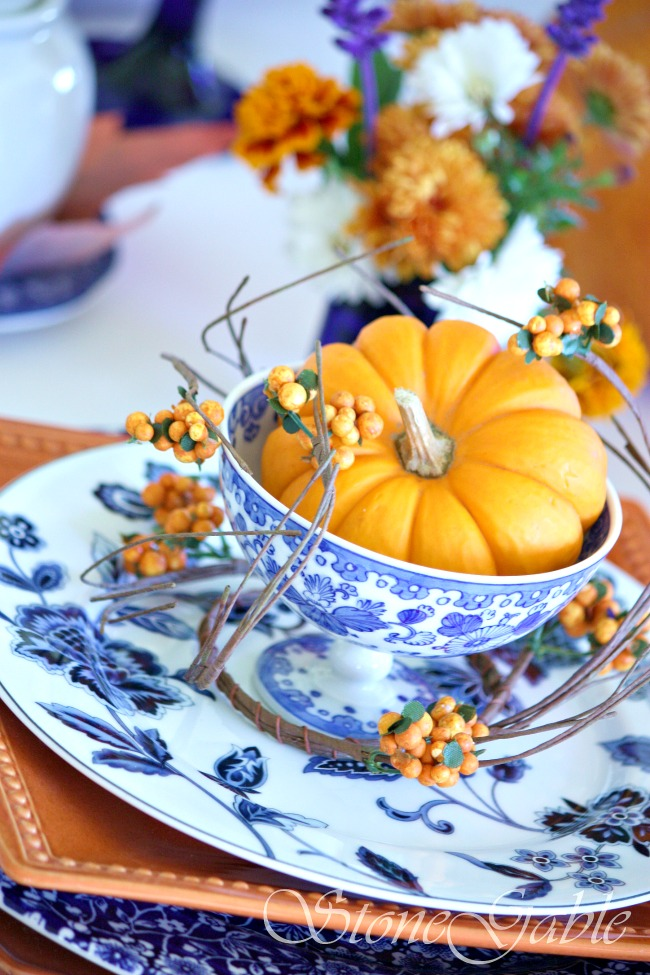 orange pumpkin in a blue and white footed bowl