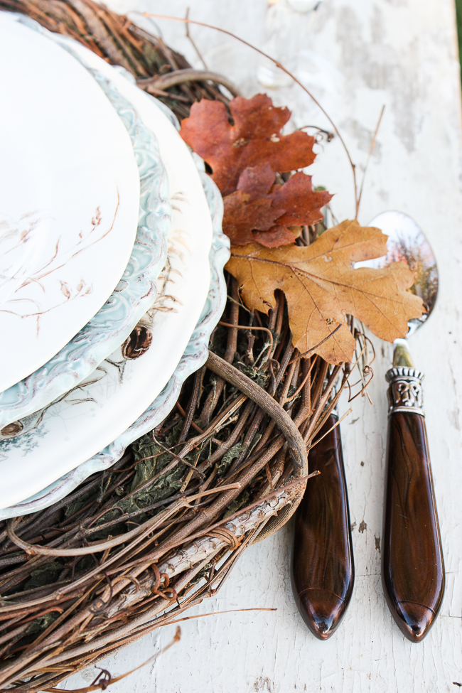 fall place setting on top of a grapevine wreath used as a charger