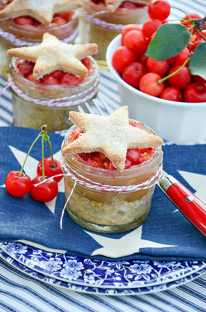 CHERRY PIE IN JARS WITH STARS- UPDATED VERSION! This is probably the quintessential summer dessert. Filled with scrumptious cherries and served with a flaky crust star these darling little pies are serve in little mason jars... as if they could not get more delightful!