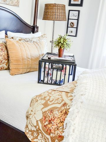 Beautiful bed made with a white coverlet and gold, bronze and white pattern. Bed tray on bed and lots of fluffy, coordinating pillows