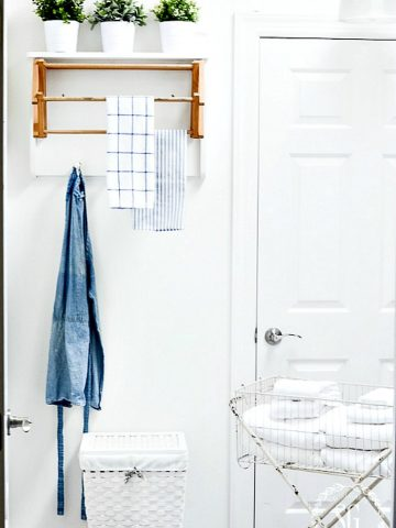 picture of a laundry room with a drying rack and a denim apron and blue and white tea towels hanging from it. This laundry room is neat and not cluttered