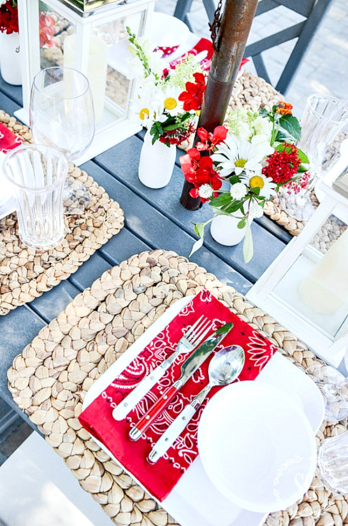outdoor table set with red and white dishes and other table items. Garden flowers and white lanterns on the table