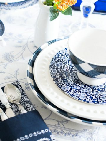plates in blue and white stacked on top of eachother with a blue and white bowl topping them off.