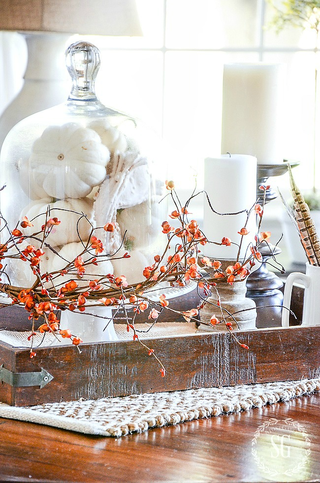 fall vignette with white pumpkins, bittersweet, feathers and candles on wooden candleholders