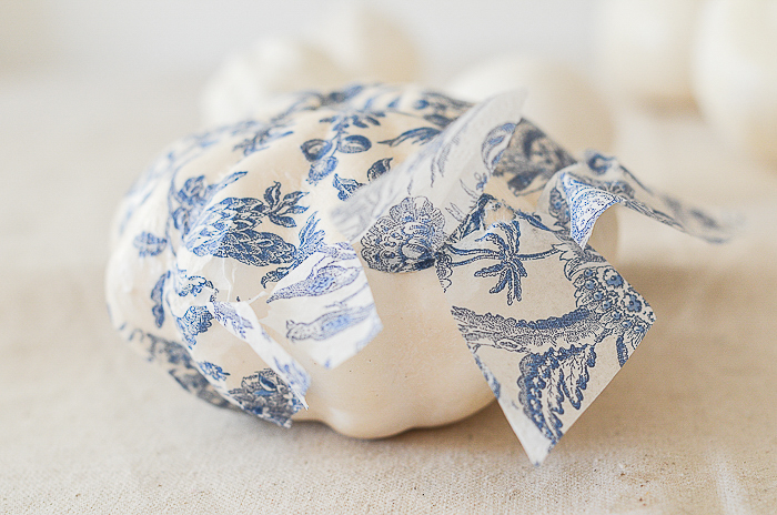 gluing down blue and white tissue paper on a pumpkin