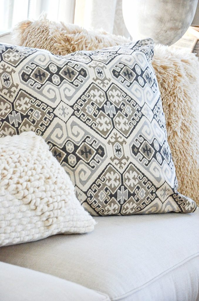 three different pillow with different textures. Wooly, patterned and fuzzy