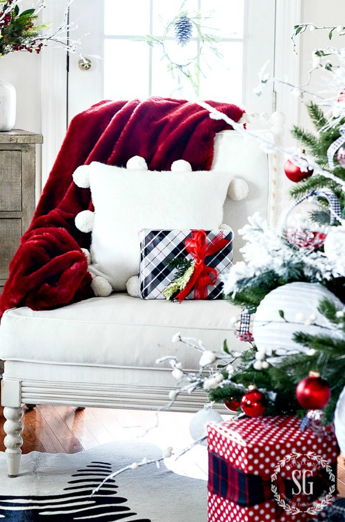 Chair with a red blanket and a plaid Christmas gift on it