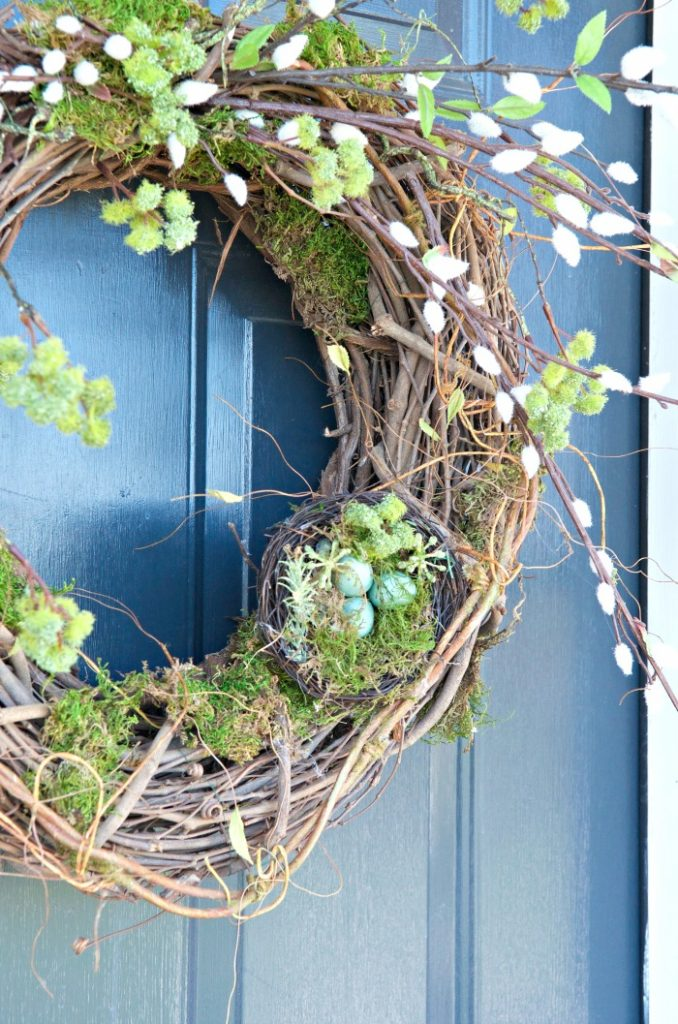 spring wreath on a blue front door. Wreath has pussy willows and nest
