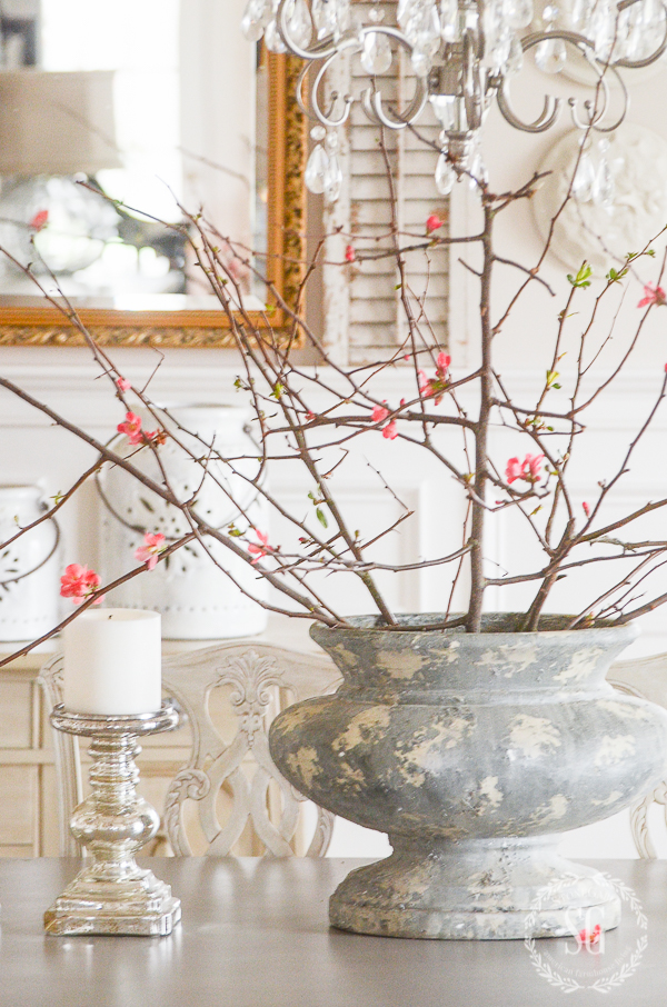 big gray urn filled with flowering crabapple blossoms