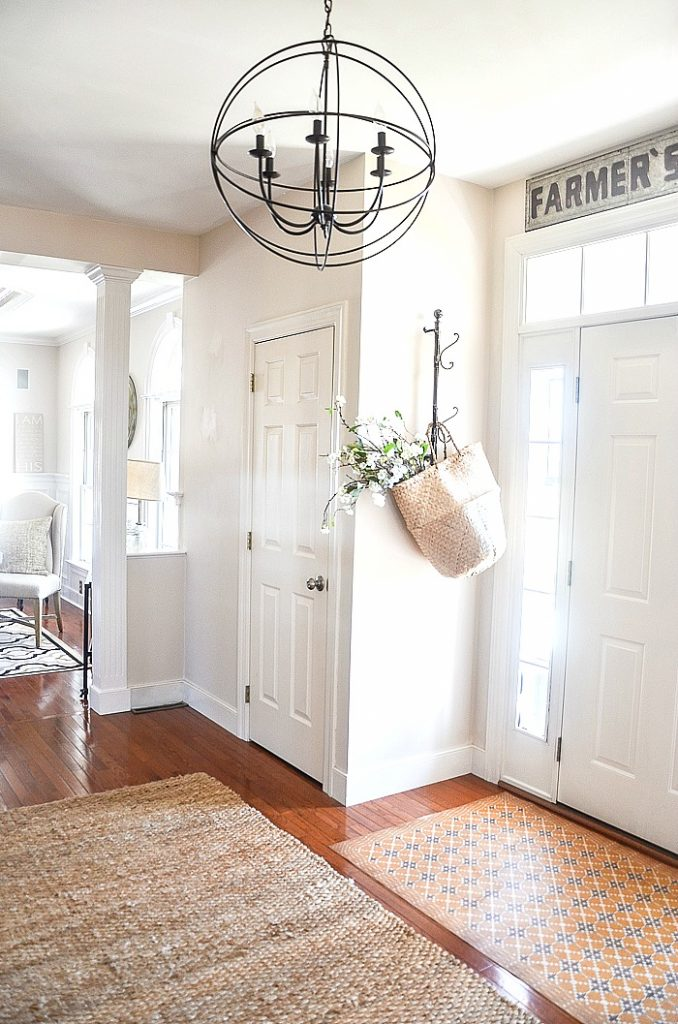 open foyer painted a neutral soft beige with white door
