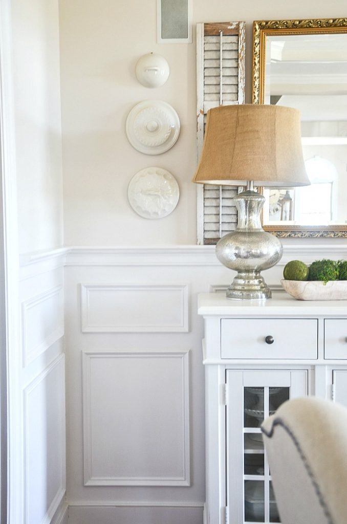 Neutral color wall with vintage lids hanging on it.
