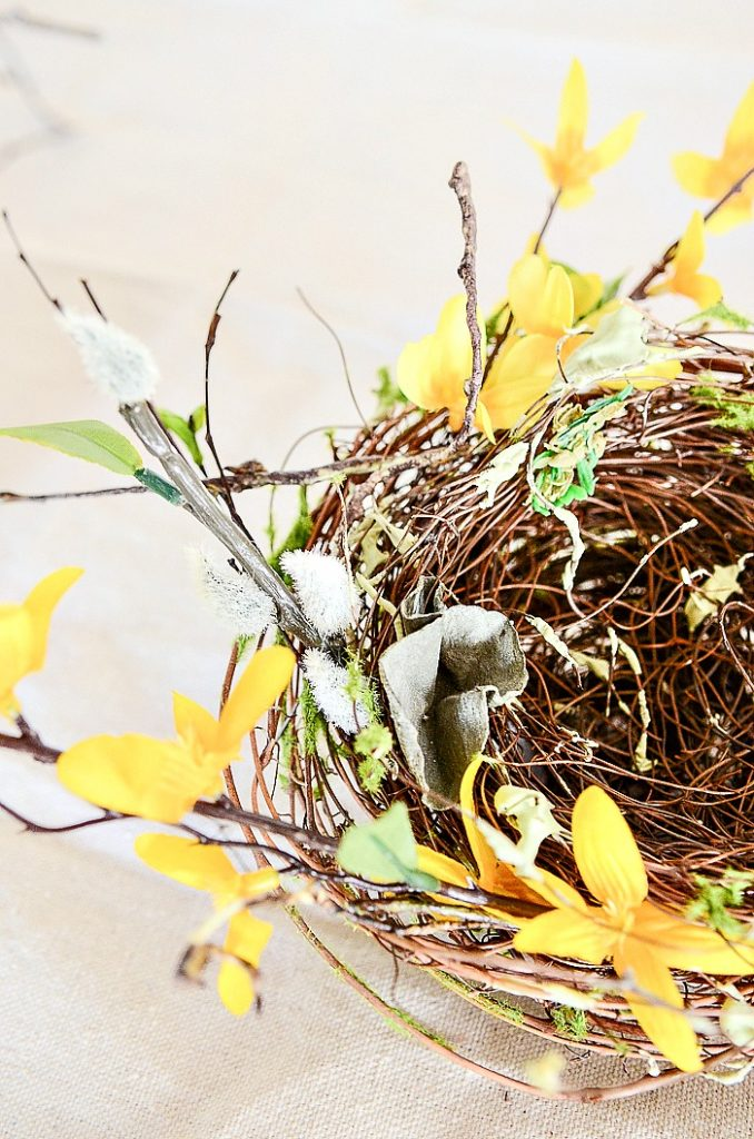 faux forsythia around a small nest