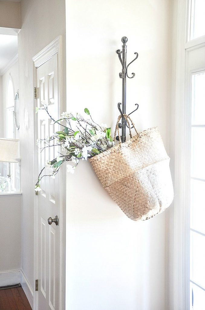 wall hooks in the foyer with a basket and flowers hanging from it