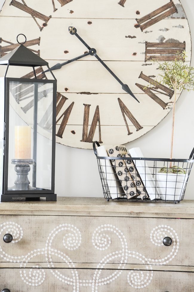 large wall clock with lantern on a buffet