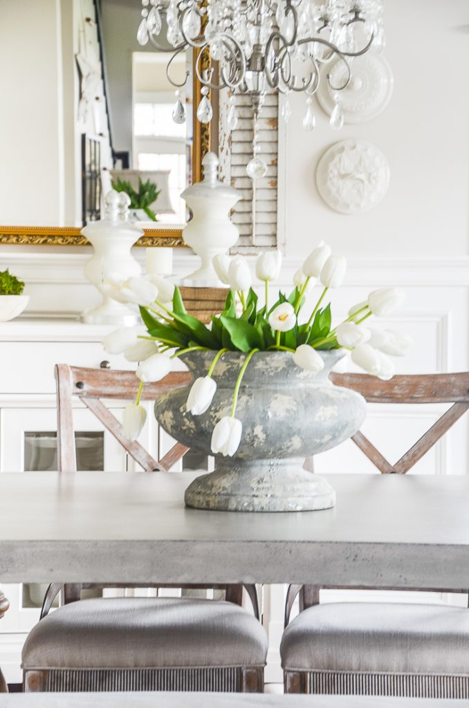 big gray urn of tulips on dining room table