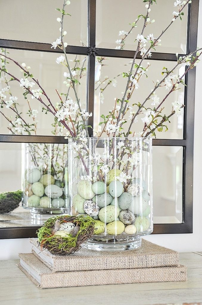 easy spring and easter arrangment has small colored eggs and faux blooms in a glass cylinder vase.