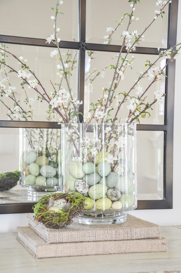 eggs and faux blooms in a glass cylinder
