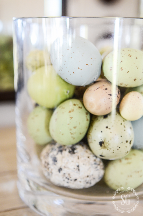 glass cylinder filled with colorful faux Easter eggs