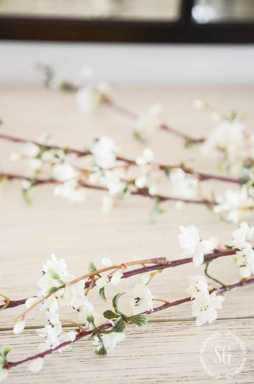faux spring branches on a table ready to be used in an easy Easter arrangement