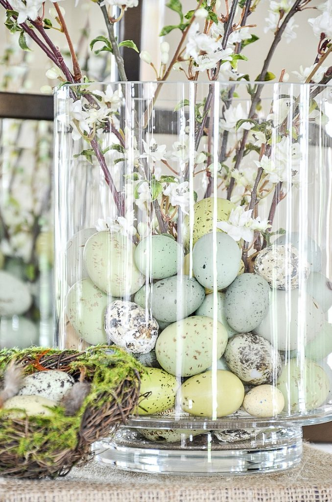 glass cylinder filled with little faux Easter eggs in an easy Easter arrangement