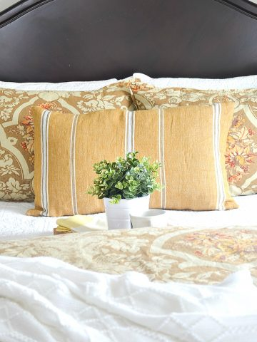 "img src;""guest bedroom"".png alt= ""Gold quilt and pillows on bed in guest room"">"