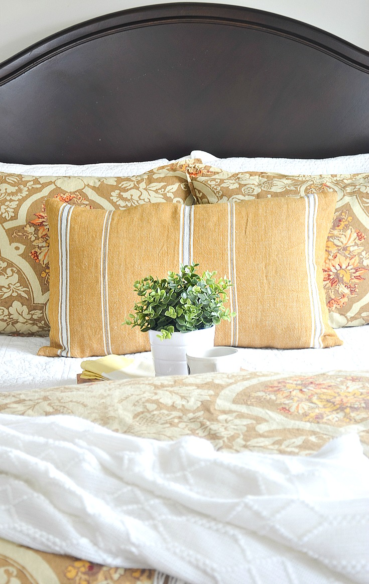 """img src;""""guest bedroom"""".png alt= """"Gold quilt and pillows on bed in guest room"""">"""