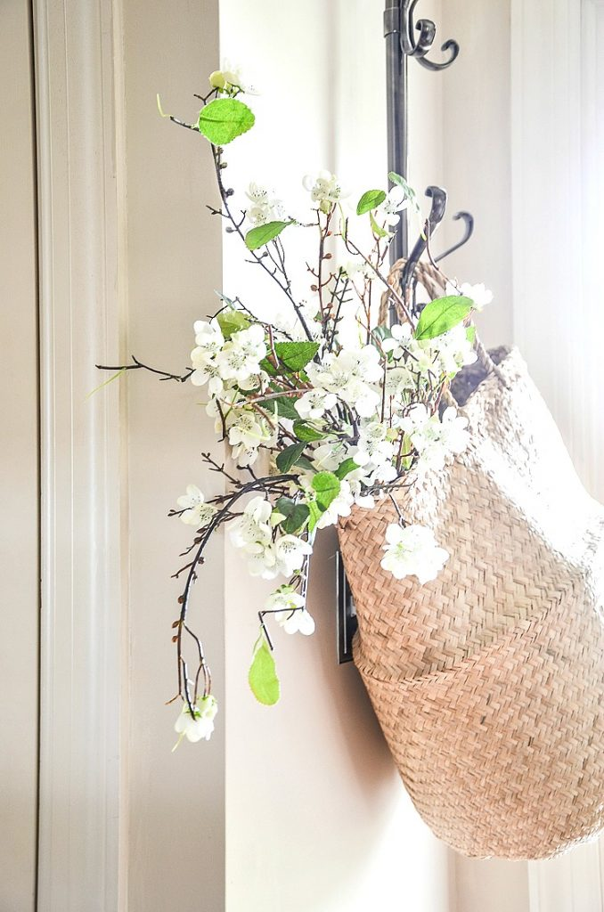 a natural material bag with white flowers hanging from a hook in the foyer