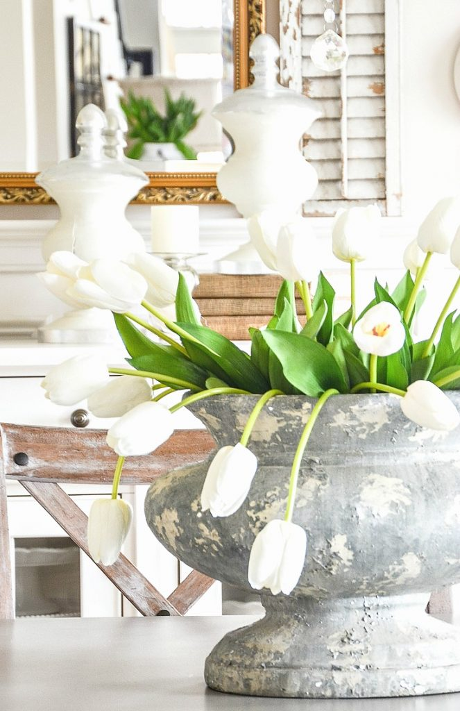 big bunch of white tulips in a stone urn