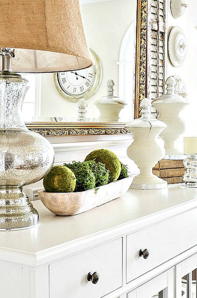 dining room sideboard with a wooden dough bowl full of moss balls