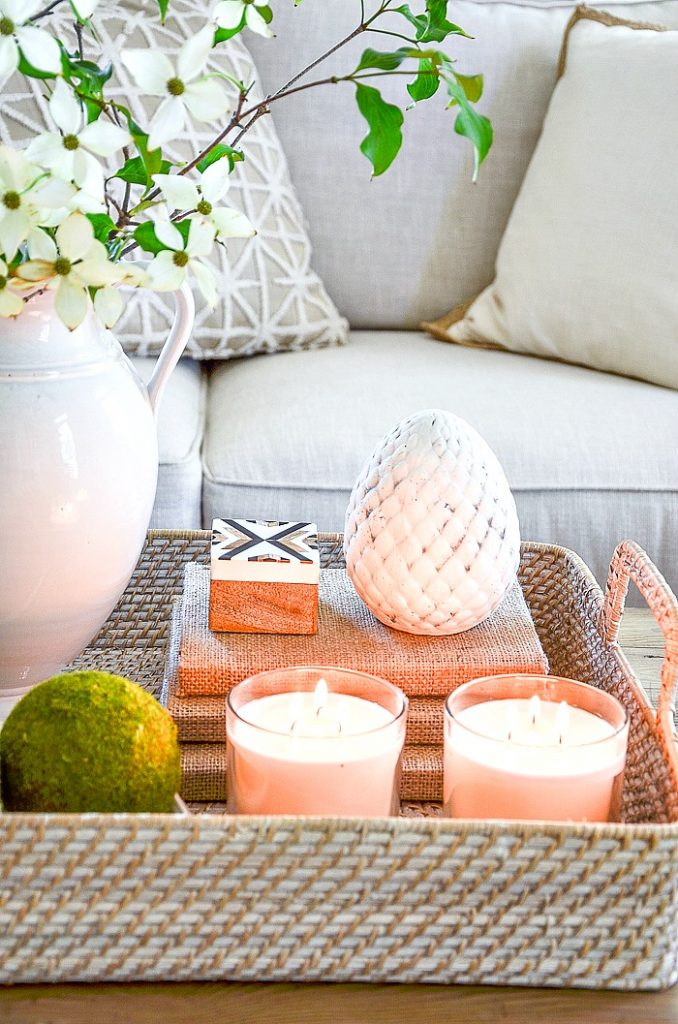 TWO CANDLES in glass candleholders are COFFEE TABLE ACCESSORIES in a basket on a table