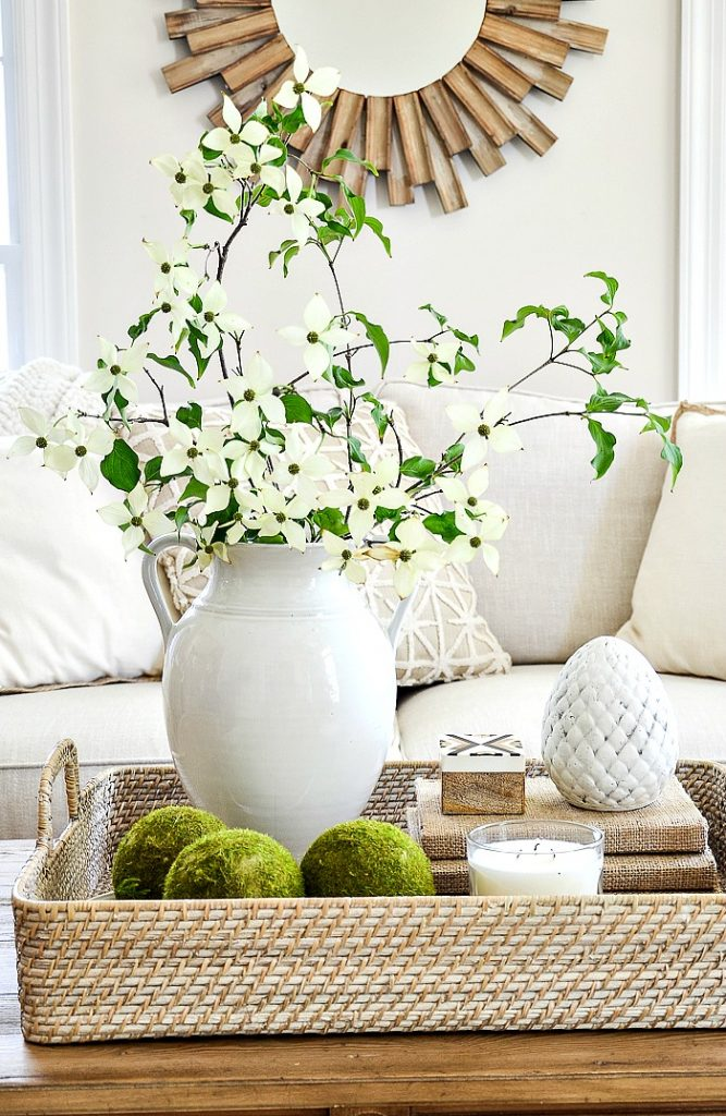 white urn on coffee table filled with white flowering dogwood branches