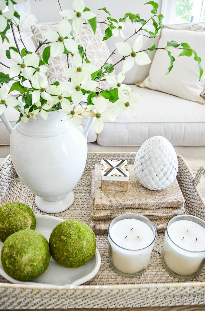 two large white candles in clear votives in a coffee table vignette
