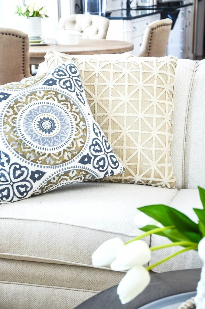 one summer decorating idea is to change out pillows. Blue and white summer pillows on a sofa