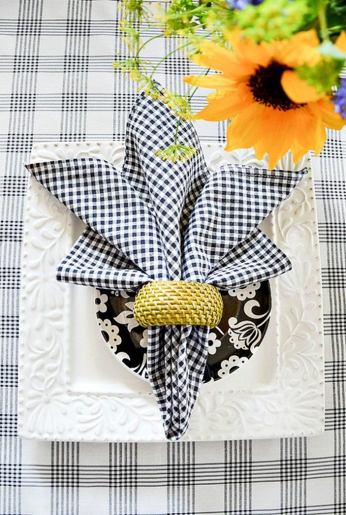 summer napkin fold with green woven napkin ring