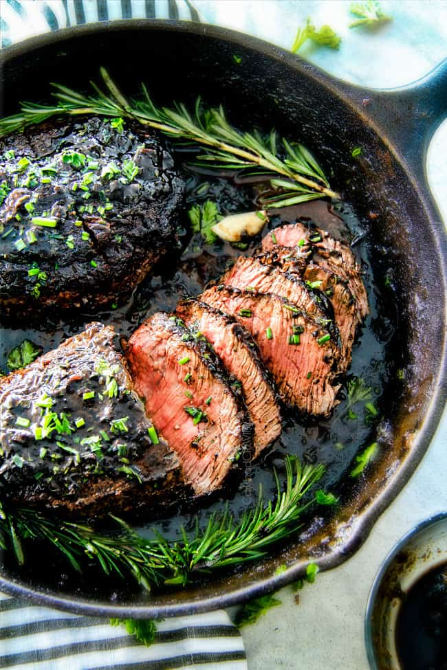 steak in a pan garnished with a sprig of rosemary
