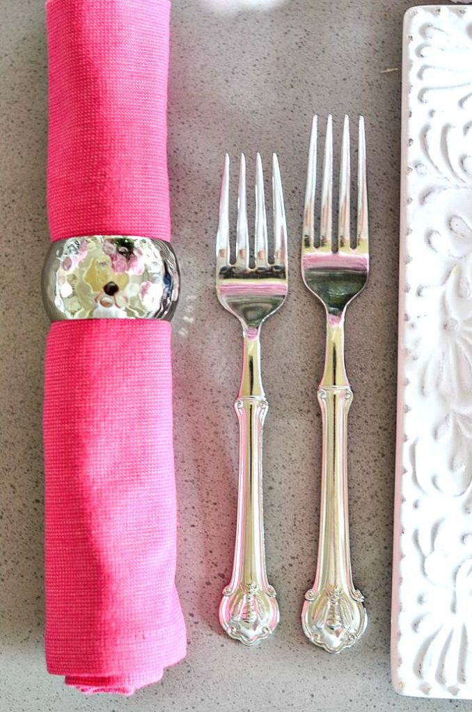 hot pink napkin roll with silver forks on a table