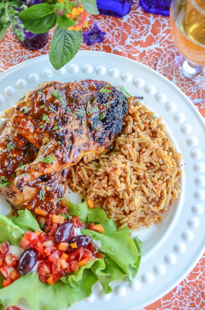 cornish game hen and rice on a white plate
